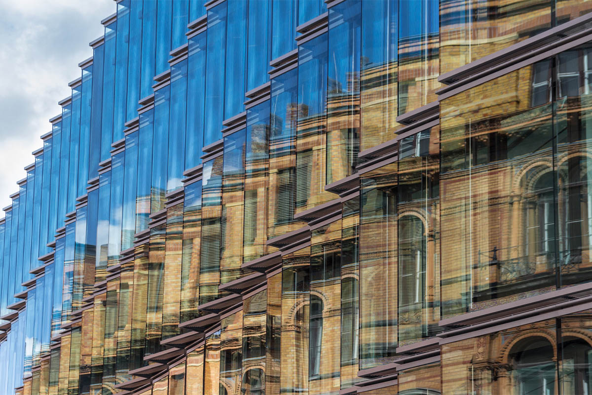 External of a building with a reflection of another building in its windows.