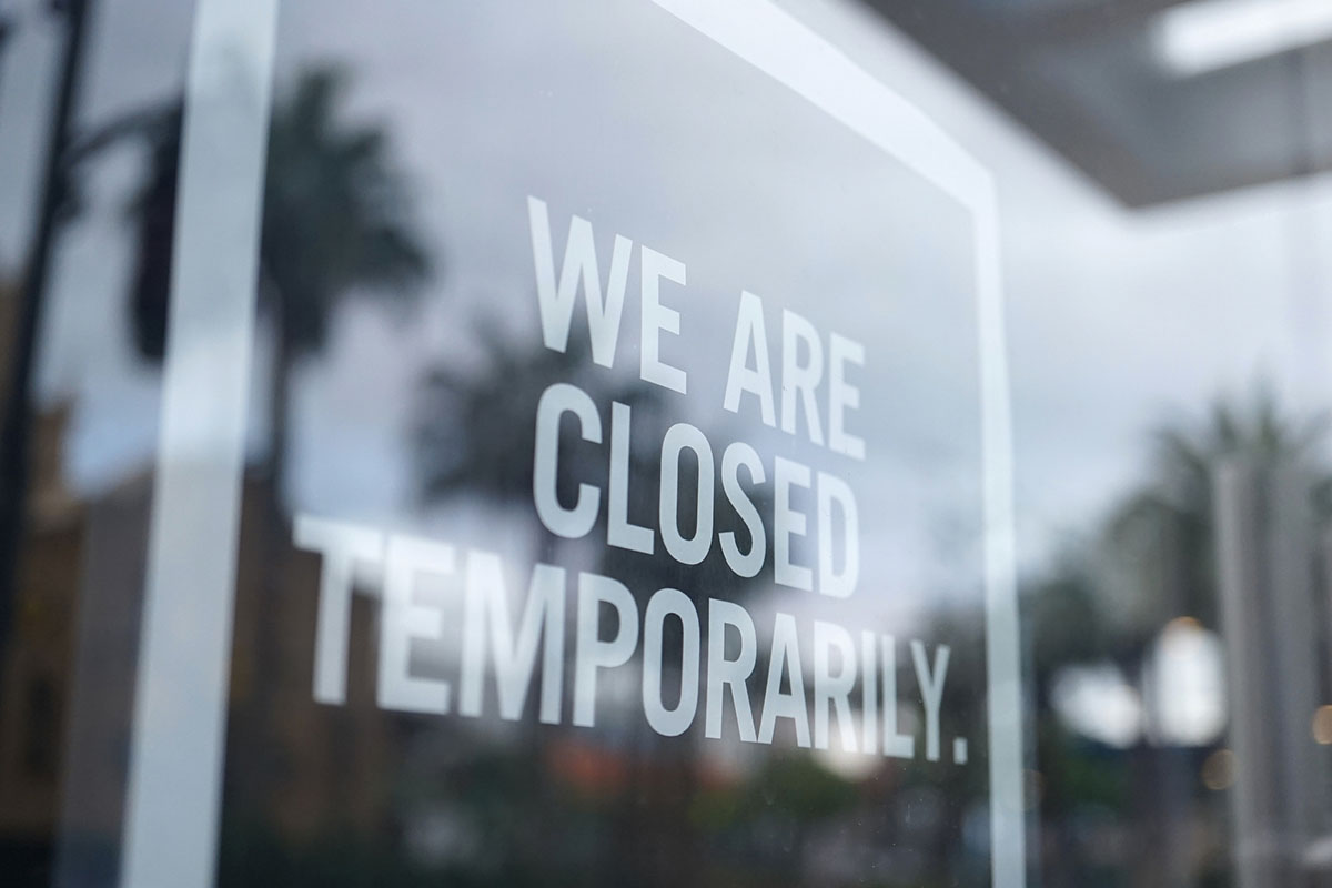 Sign hanging in a store window that says We Are Closed Temporarily