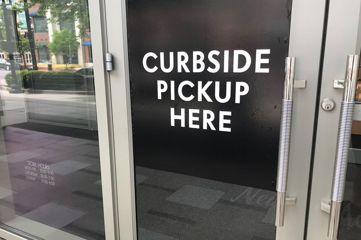 A white sign naging on a glass door that reads Curbside Pickup Here