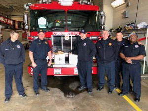 Group of Columbus Firemen in front of their truck with boxes of donated meal delivery from Cooper's Hawk at Easton.