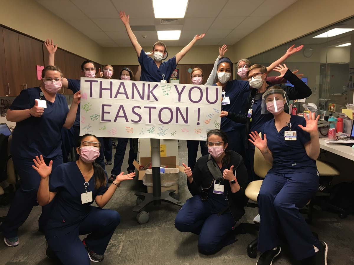 Large group of masked healthcare workers around sign reading 'Thank You Easton.'