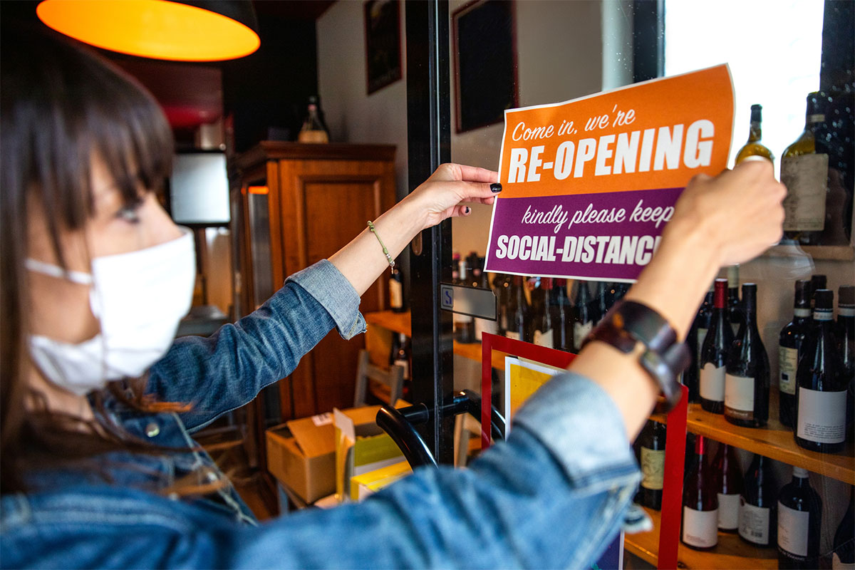 A woman wearing a face mask taping a sign to her store window that reads Cone In, We're Re-Opening. Kindly Please Keep Social-distance.
